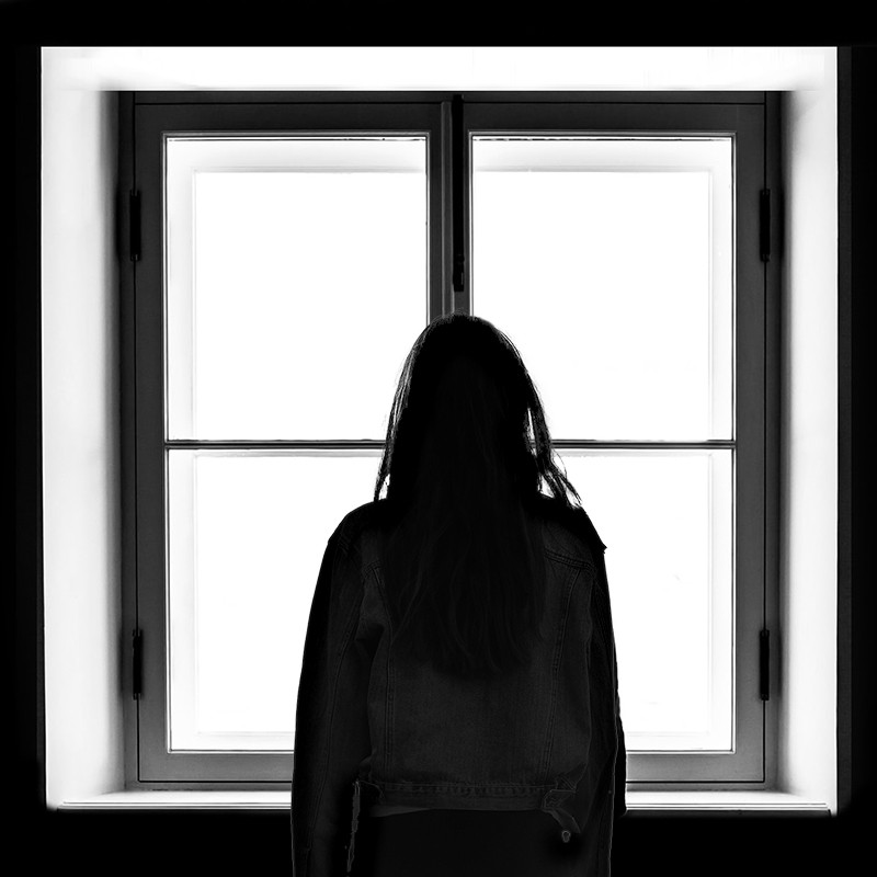 silhouette of woman standing in front of window