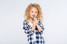 baby girl with microphone smiling singin