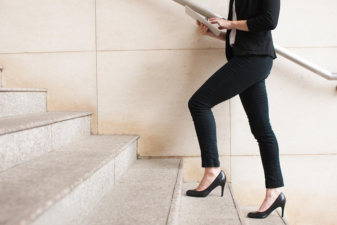 Businesswoman walking upstairs and using