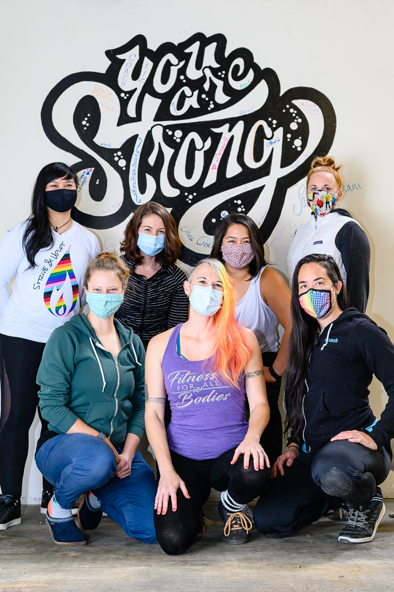 "A team of personal trainers with masks on in front of bold print ""You are Strong"" on wall."