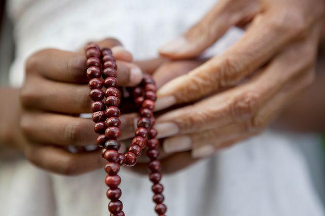 Hands holding prayer beads