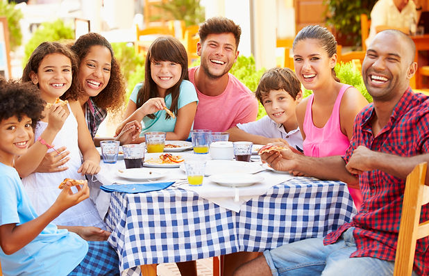 Two Families Eating Meal At Outdoor Rest