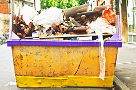 image of a skip bin overloaded with rubbish going everywhere falling out of the skip bin