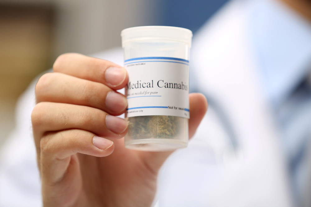 Physician Holding a Jar of Medical Cannabis