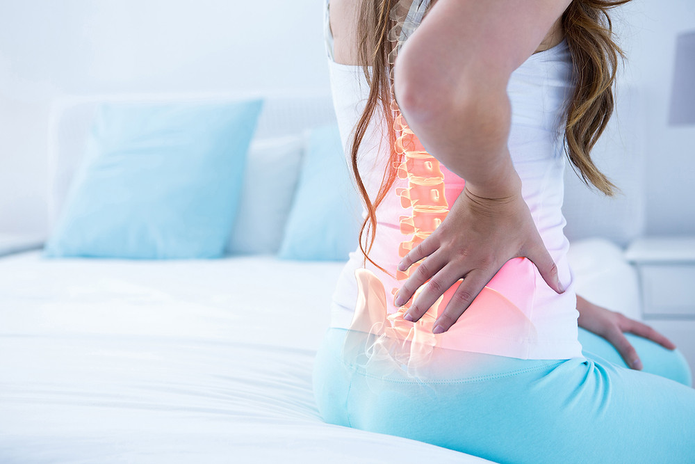 Woman Sitting Up and Holding Her Back with X-Ray Effect Applied to Show Spine in Red to Designate Pain