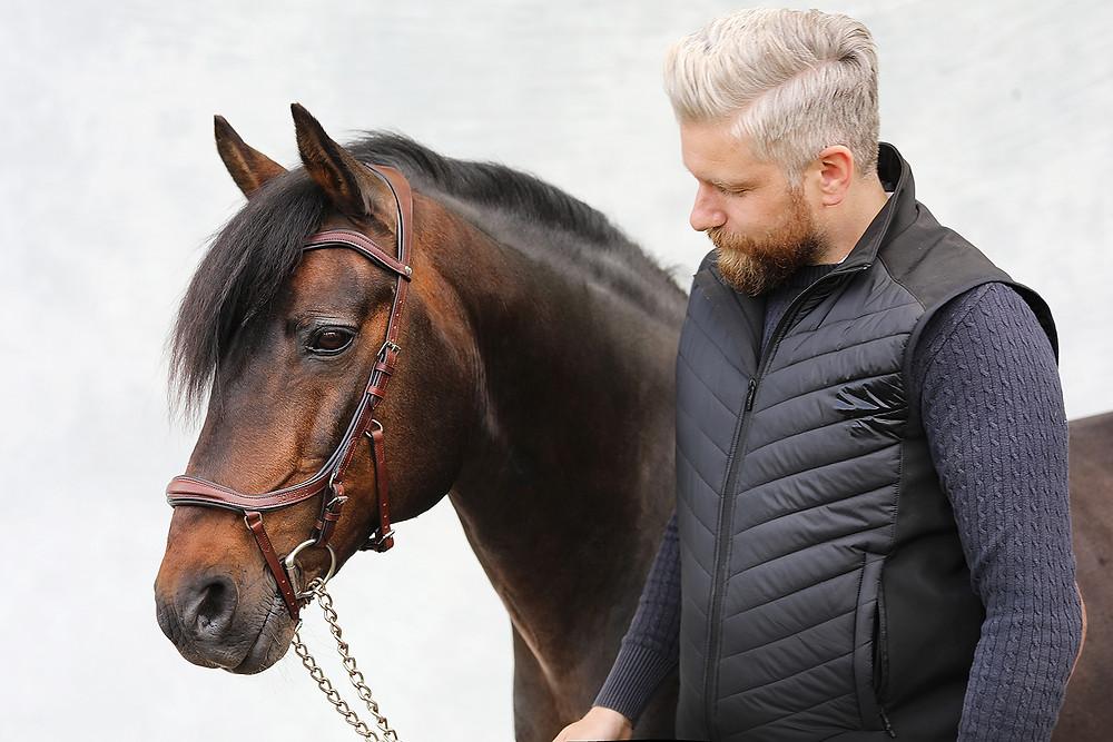 En brun ponny och en man som håller den