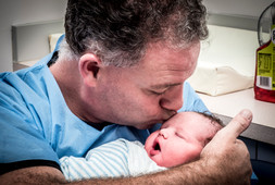 Dad-kissing-his-son-still-wearing-his-scrubs-from-the succesful-Cesarean-section-birth-Perth-Birth-P