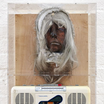 Lynn Hershman Leeson, Self-Portrait as Albino (detail), 1968, wax face cast, bronze powder, makeup, wig, scarf, sensors, sound file, and recorder mounted on board