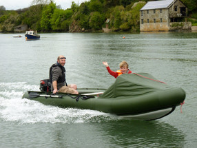 Person and child on an inflatable motor canoe Spearfish