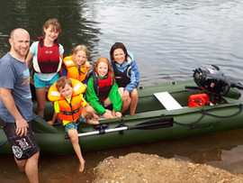 Family of five looking happy with their inflatable dinghy