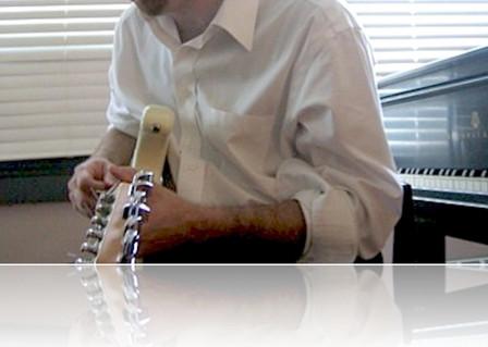 Jim+playing+guitar+at+piano_reflection.j