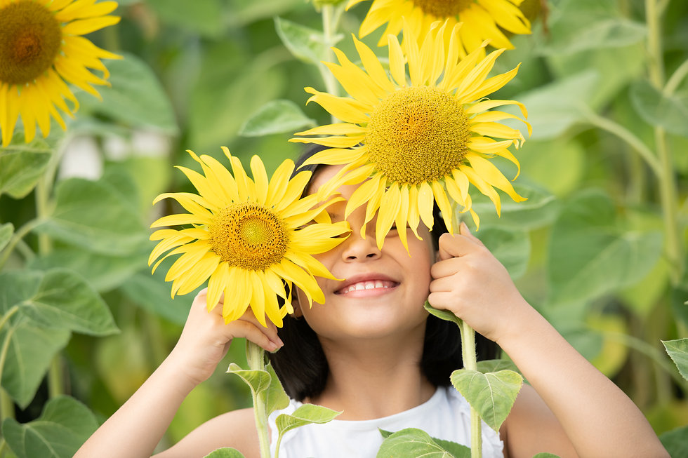 happy-little-asian-girl-having-fun-among-blooming-sunflowers-under-the-gentle-rays-of-the-