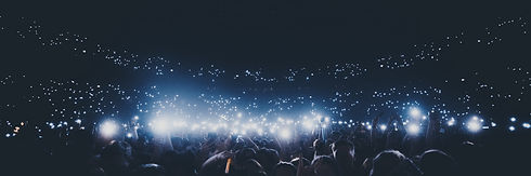 Music - crowd with phone lights in dark.