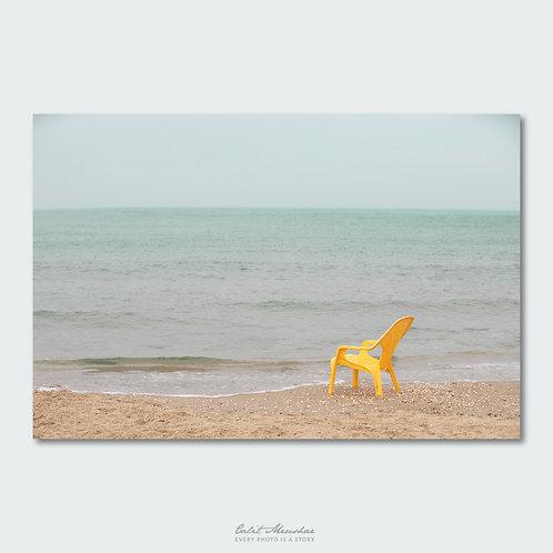 כיסא צהוב בודד בחוף הים