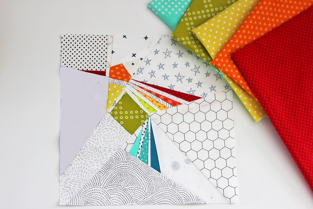 different cut out fabrics on the table - how to paper piece quilting