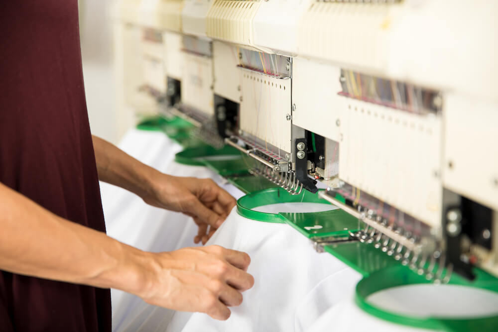 man operating a machine embroidery