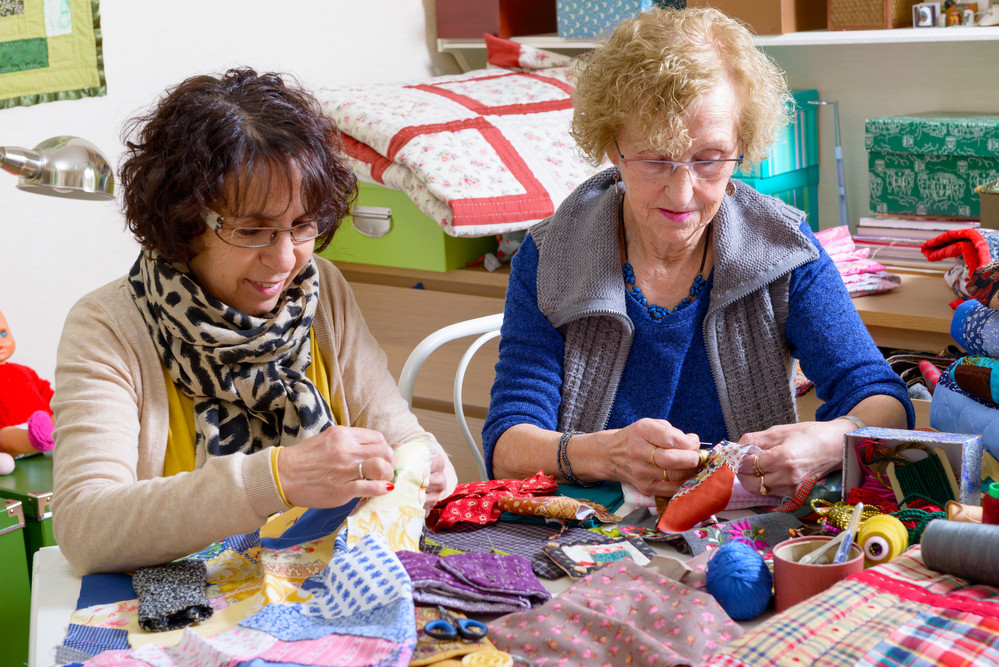 Two women quilting with fabric panels