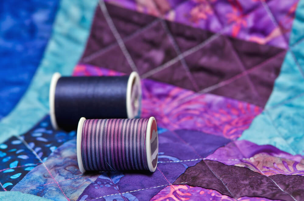 thread rolls on a patchwork - quilting thread vs embroidery thread