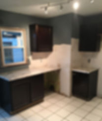 Kitchen with white stone flooring tiles. Dark cabinets and marble countertops