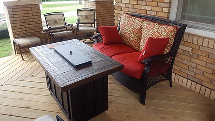 Patio deck with outdoor furniture. Red pillows on black wicker chairs.