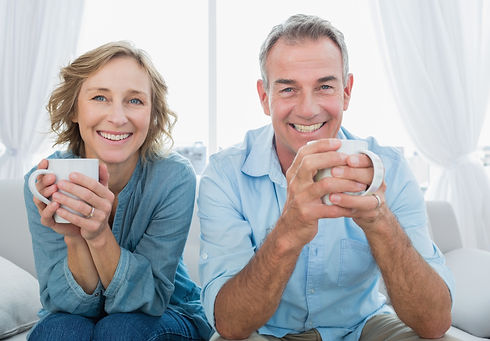 Smiling-middle-aged-couple-sitting-on-th