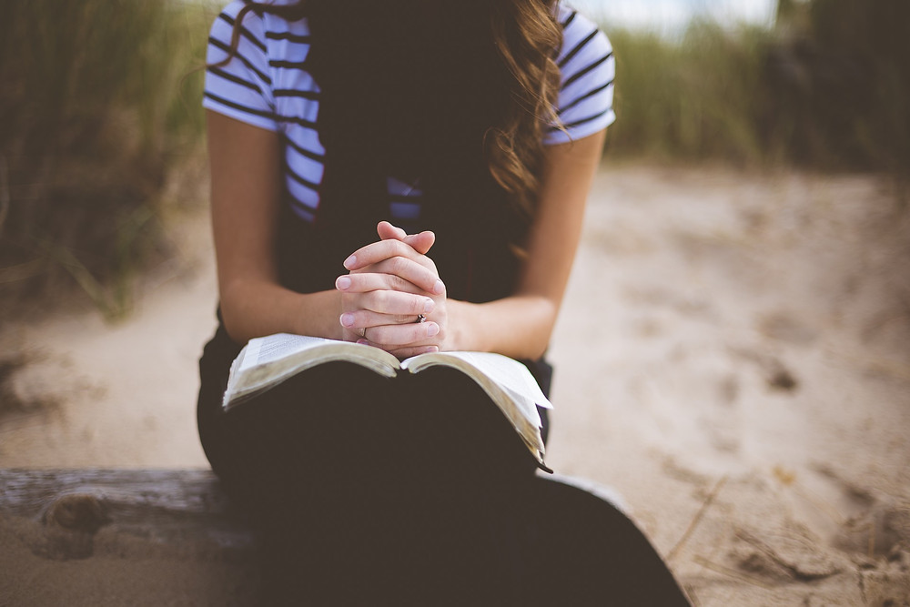 Girl praying with Bible