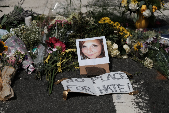 JUSTIN IDE / REUTERS Flowers and a photo of car-ramming victim Heather Heyer lie at a makeshift memorial in Charlottesville, Virginia.