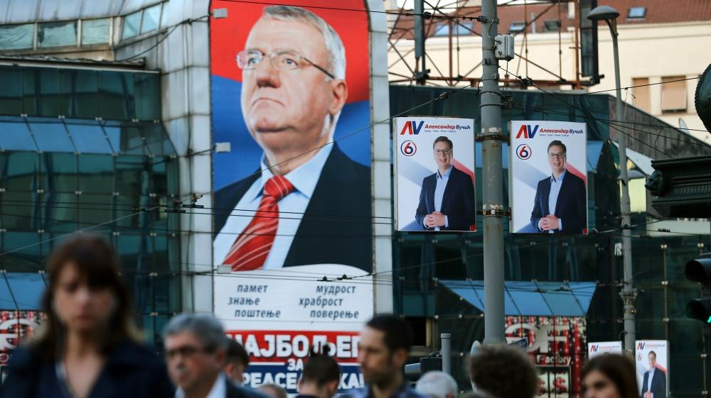 People walk past posters of Seselj and Serbian President Aleksandar Vucic in 2017 [File: Reuters]