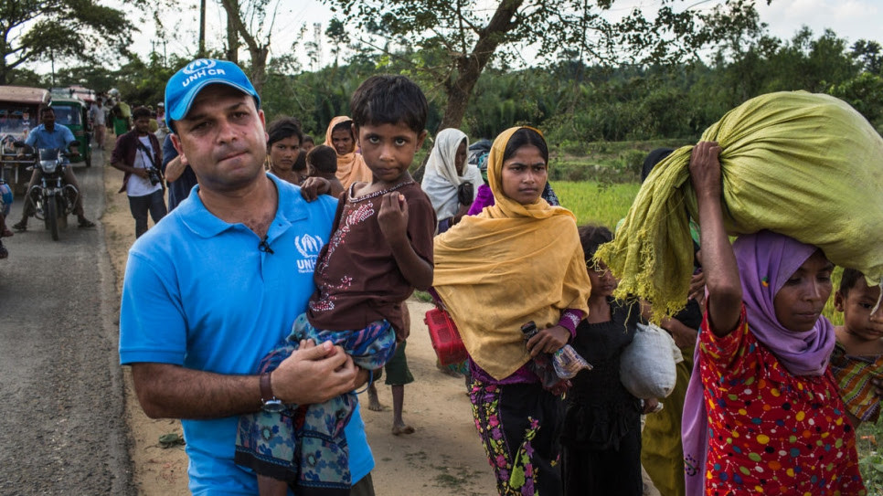 UNHCR spokesman Mohammed Abu Asaker carries Noor Kalima, 4, on the 10-kilometre walk from Myanmar to Kutupalong refugee settlement in Bangladesh. Noor's parents were killed when their village was attacked. Both she and her sister, Umme Salma (wearing black), are being cared for by their aunt, Rabiaa Khatun (wearing orange headscarf). © UNHCR/Andrew McConnell