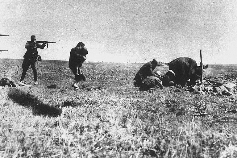 A German soldier aiming his rifle at a woman and her child in Ivangorod, Ukraine, in 1942.