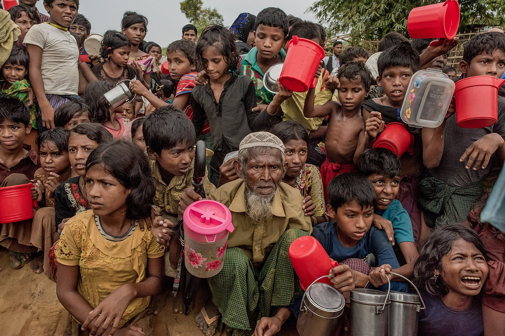 Rohingya refugees jostling for aid at a hot meal distribution center in Palongkali refugee camp. CreditTomas Munita for The New York Times