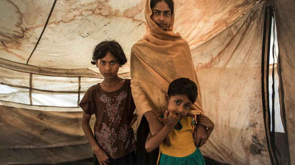 Rabiaa Khatun and her nieces, Umme Salma, 8, and Noor Kalima, 4, stand inside a shelter at a transit camp near Kutupalong camp in Bangladesh.  © UNHCR/Andrew McConnell
