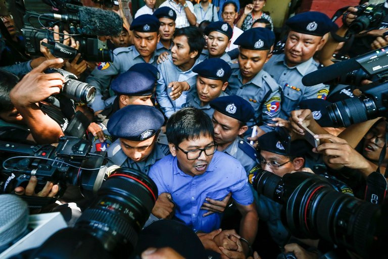 The Reuters journalists U Wa Lone, center front, and U Kyaw Soe Oo, center back, were escorted by the police in Yangon, Myanmar, on Wednesday, after being charged with obtaining state secrets. Credit Lynn Bo Bo/European Pressphoto Agency