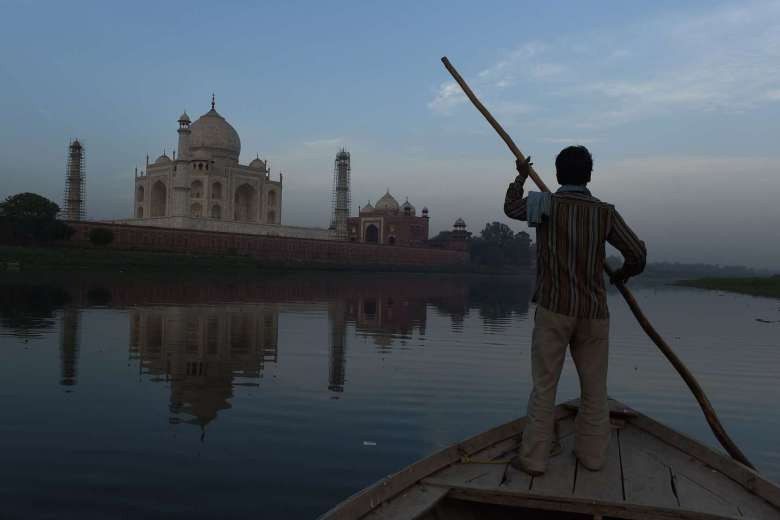Indian boatman Banwari rows his boat on the Yamuna River behind the Taj Mahal in Agra on April 16, 2016. PHOTO: AFP