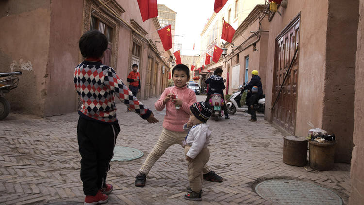 In this Nov. 4, 2017, photo, children play in the old city district where Chinese national flags are prominently hung in Kashgar in western China's Xinjiang region. (Ng Han Guan / AP)