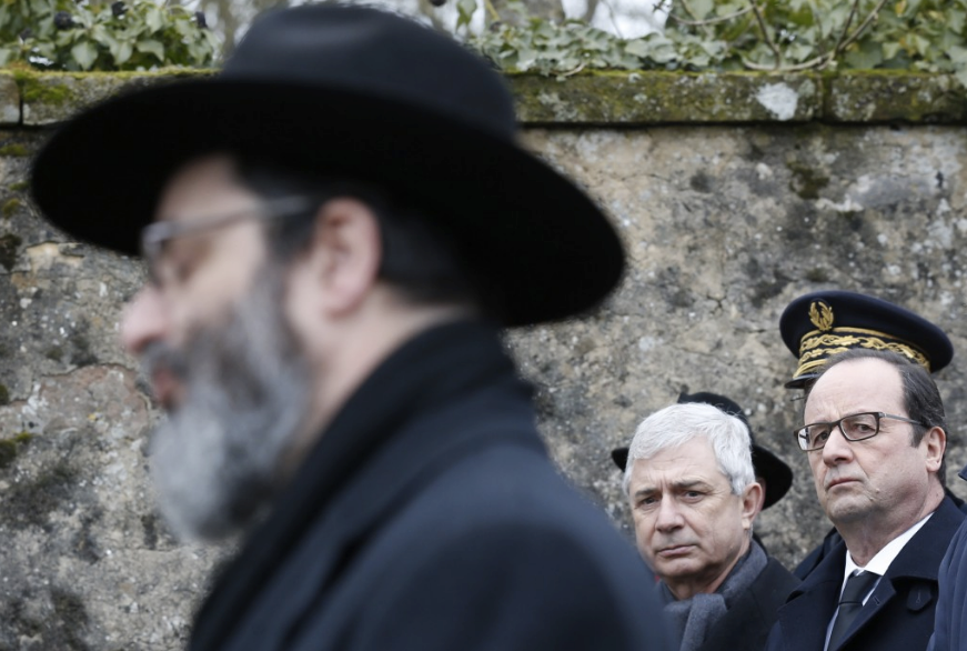 French President François Hollande, right, and French National Assembly Speaker Claude Bartolone, center, attend a ceremony during a visit to a Jewish cemetery in France last year. (Vincent Kessler/Pool/European Pressphoto Agency)