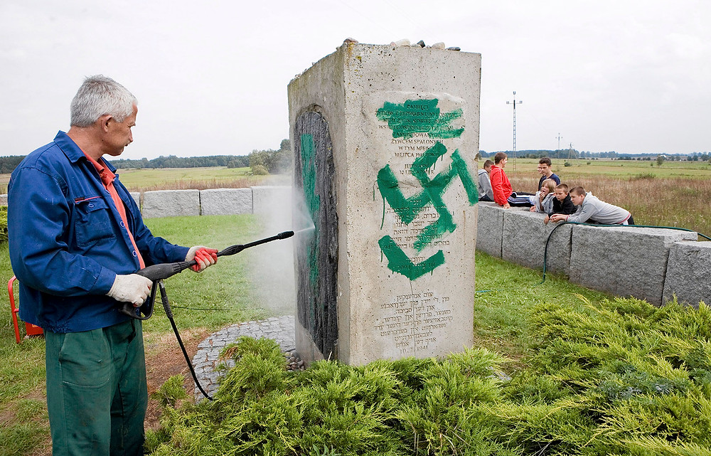 Jendrzej Wojnar/Agencja Gazeta/Reuters A worker cleaning a memorial to the victims of the 1941 Jedwabne pogrom after it was defaced by neo-Nazis, Poland, 2011