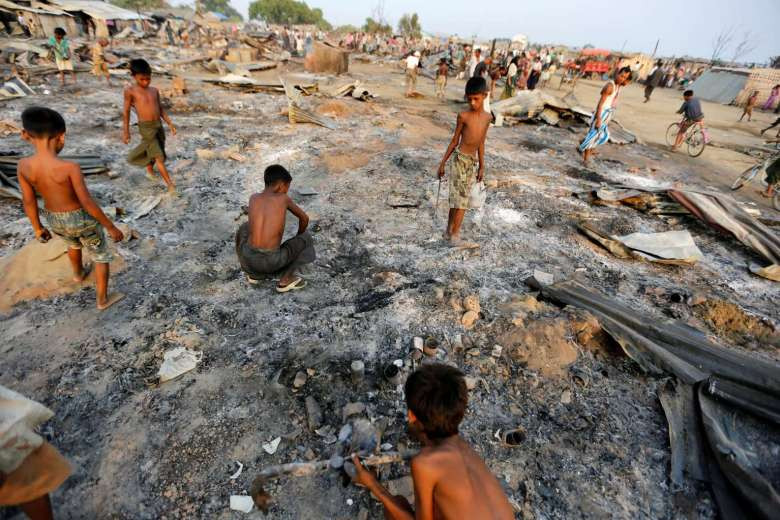 Boys search for useful items among the ashes of burnt houses after fire destroyed shelters at a camp for internally displaced Rohingya Muslims in the western Rakhine State near Sittwe, Myanmar on May 3, 2016. PHOTO: REUTERS