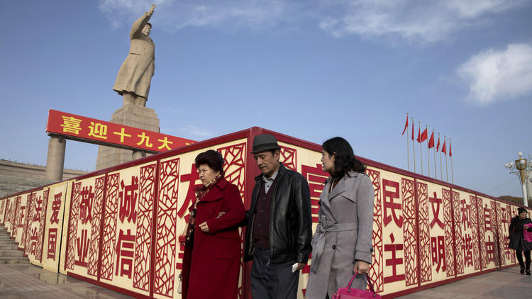 "In this Nov. 4, 2017, photo, residents walk past a statue showing Mao Zedong near billboards with the words for ""Welcome 19th Congress,"" ""Patriotism"" and ""Democracy"" near a square in Kashgar in western China's Xinjiang region. (Ng Han Guan / AP)"
