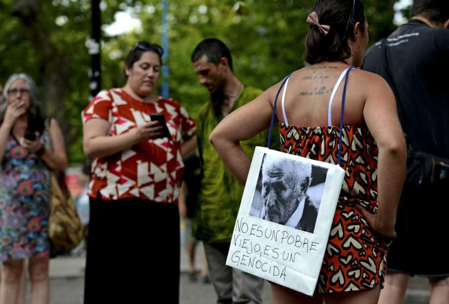 "A woman stands with a picture of former police officer Miguel Etchecolatz that reads in Spanish, ""He is not a poor man, he is a genocide"" during a protest in Mar del Plata, Argentina, Friday, Dec. 29, 2017. Etchecolatz was sentenced to life in prison for crimes against humanity during Argentina last dictatorship but a court in Argentina has granted him house arrest Wednesday, due to health problems"