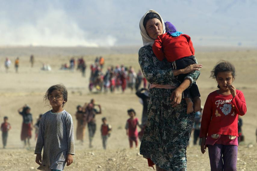 Displaced people from the minority Yazidi sect, fleeing violence from forces loyal to the Islamic State in Sinjar town, walk towards the Syrian border on the outskirts of Sinjar mountain near the Syrian border town of Elierbeh of Al-Hasakah Governorate. REUTERS