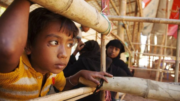 Image captionNoor Kalima, who witnessed the murder of her parents, waits in a wooden pen to be processed.