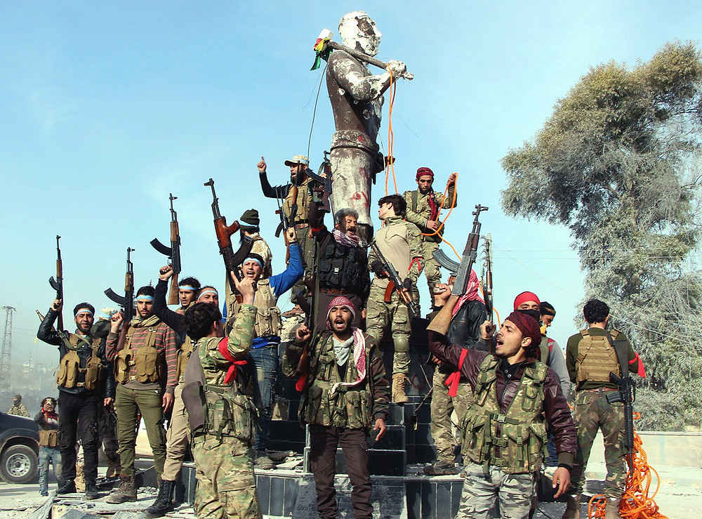 Turkish-backed Syrian National Army fighters preparing to destroy a statue of Kaveh, a heroic figure in Kurdish mythology, in Afrin, Syria, March 18, 2018. Hasan Kırmızitaş/DHA-Depo Photos via AP