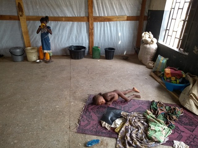 A displaced child sleeps naked in a classroom while another child scoops drinking water from open bucket in Ayiin camp. The rest of the IDPs are outside to receive food items.
