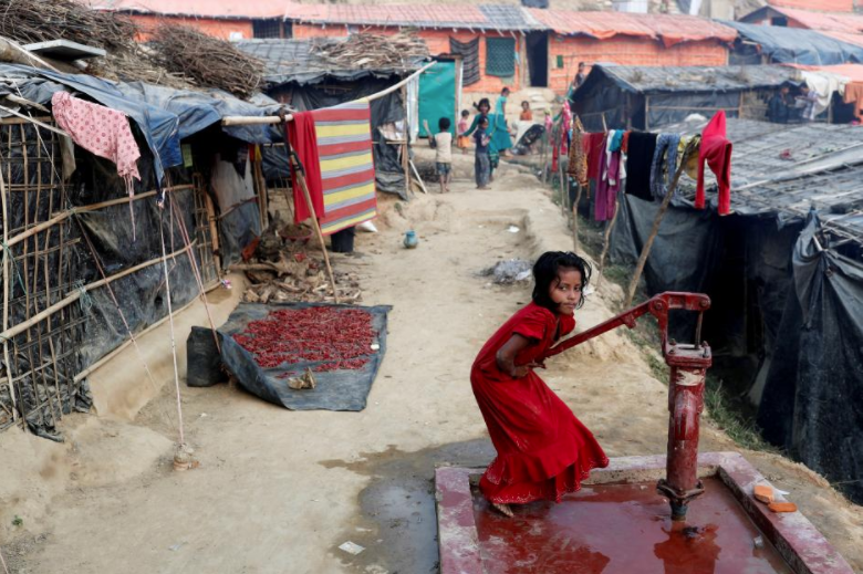 A Rohingya refugee girl plays at a tube-well in Palong Khali camp, near Cox's Bazar, Bangladesh January 14, 2018. REUTERS/Tyrone Siu