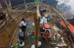 FILE PHOTO: A Rohingya refugee family eats as they sit inside their semi constructed shelter at Kutupalong refugee camp near Cox's Bazar, Bangladesh October 24, 2017. REUTERS/Adnan Abidi