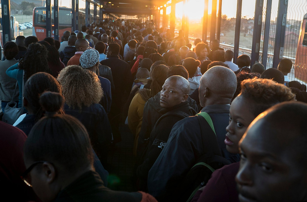 Commuters on their way to work wait to board a bus at the station in Soweto. Arguably, the greatest casualty of the Gupta-Bell Pottinger campaign is the very cause it nominally championed: helping impoverished blacks. Credit Joao Silva/The New York Times