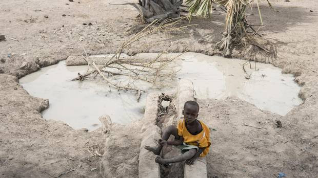 "A boy sits beside a fetid pool of water in Aweil, South Sudan, in early March. A leaked UN report says spreading famine in the region is due to the ""cumulative toll"" of deliberate government actions. (Mackenzie Knowles-Coursin/AP)"