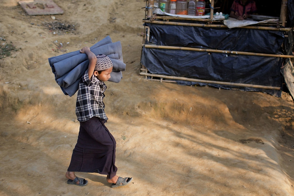 A Rohingya Muslim child carrying a blanket at Kutupalong refugee camp in Ukhiya, Bangladesh, Thursday, Dec. 21, 2017. Many thousands of Rohingya people have crossed over from Myanmar into Bangladesh. (A.M. Ahad/Associated Press)