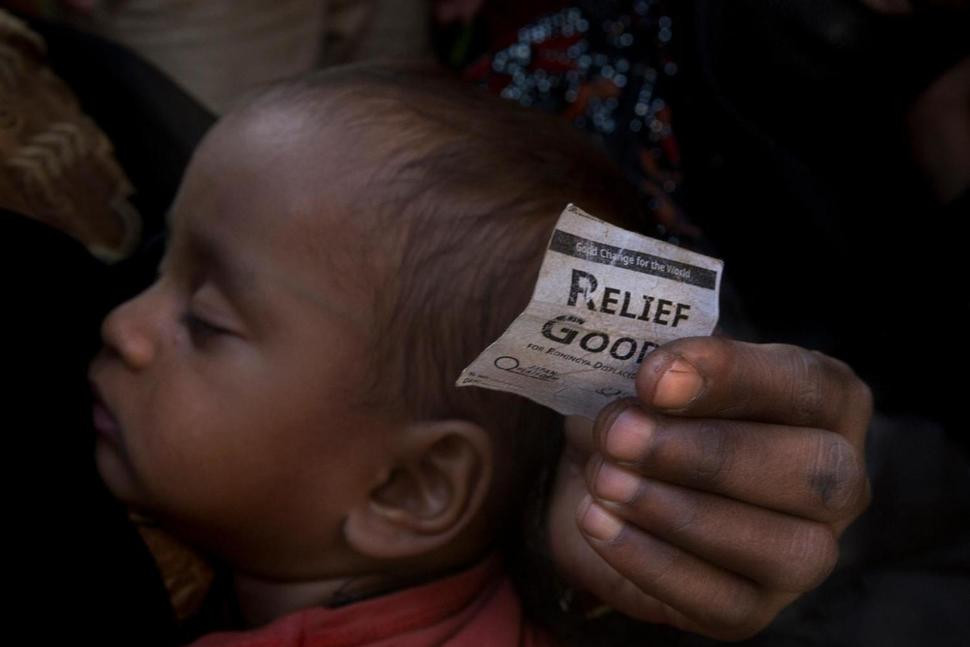 A Rohingya refugee woman holds a relief coupon and her child as she waits in a queue outside a distribution center at Kutupalong near Cox's Bazar, Bangladesh, Monday, Jan. 22, 2018. The gradual repatriation of more than 650,000 Rohingya Muslim refugees back to Myanmar from Bangladesh, scheduled to begin Tuesday, has been postponed amid widespread fears that refugees would be forced to return, a Bangladesh official said Monday. (AP Photo/Manish Swarup) The Associated Press
